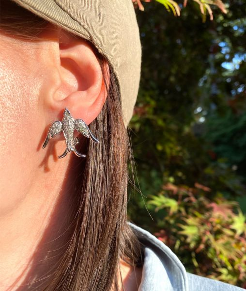 Christian Dior swallow earrings worn with hat